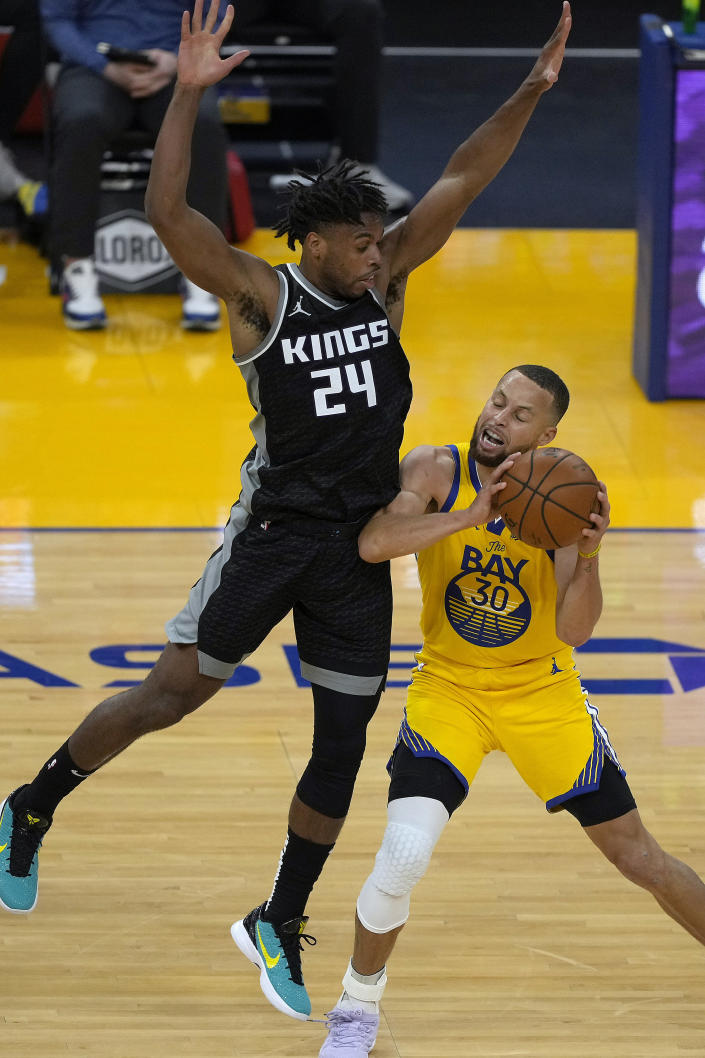 Golden State Warriors guard Stephen Curry (30) reacts as he is fouled by Sacramento Kings guard Buddy Hield (24) during the first half of an NBA basketball game on Sunday, April 25, 2021, in San Francisco. (AP Photo/Tony Avelar)