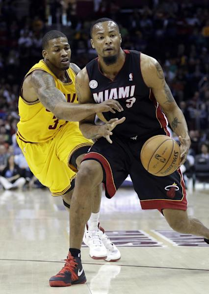 Cleveland Cavaliers' Alonzo Gee, left, tries to knock the ball away from Miami Heat's Rashard Lewis in the first quarter of an NBA basketball game Monday, April 15, 2013, in Cleveland. (AP Photo/Mark Duncan)