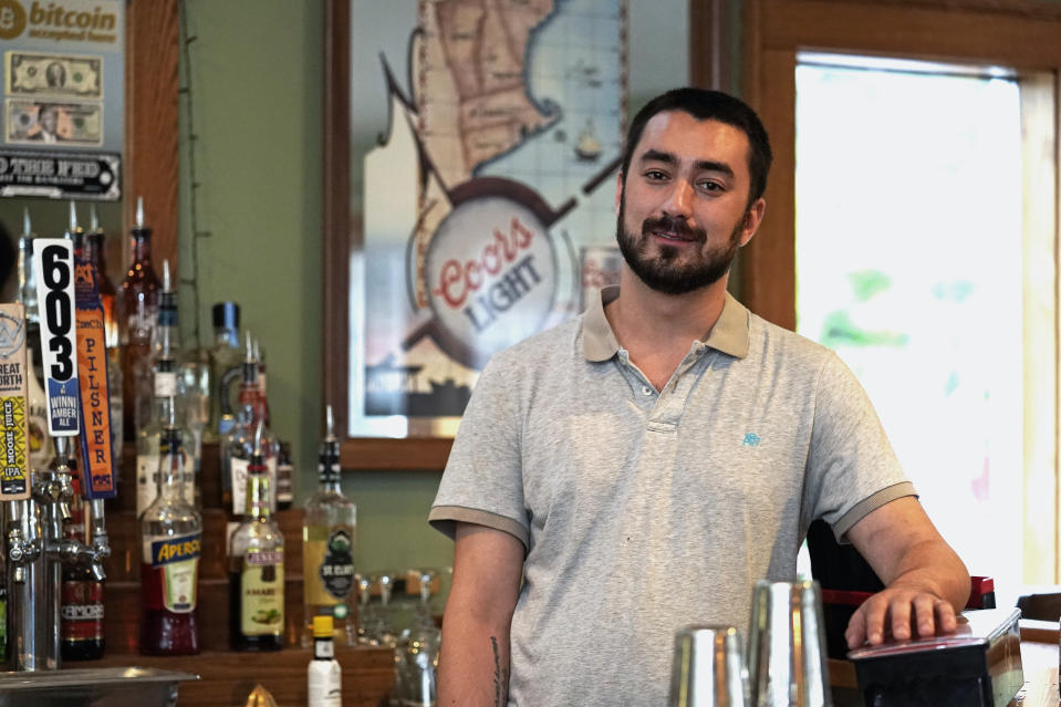 David Culhane, owner of the White Mountain Tavern, Tuesday, July 13, 2021, poses at the bar of his business in Lincoln, N.H. Culhane was fined $1,000 by the New Hampshire Attorney General's office, and later reached a settlement, for holding a live music performance in November 2020, where people crowded together and employees did not wearing masks. A provision in the recently signed New Hampshire state budget will provide refunds to businesses that were fined for violating the governor's pandemic emergency orders. (AP Photo/Charles Krupa)
