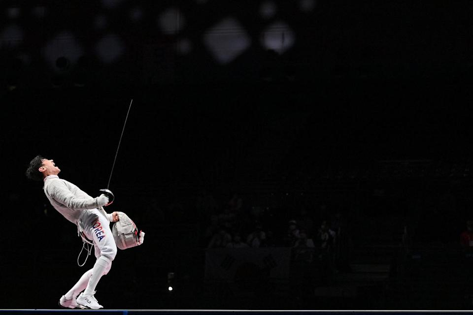 <p>South Korea's Gu Bongil celebrates scoring a point against Italy's Luca Curatoli in the men's sabre team gold medal bout at the Makuhari Messe Hall on July 28.</p>