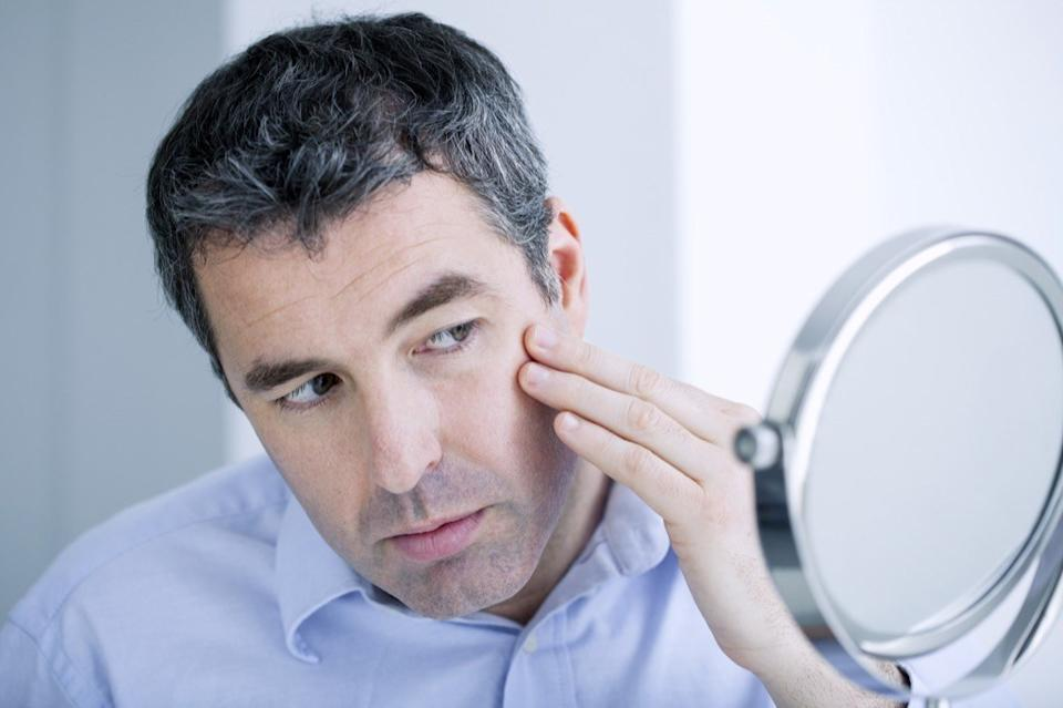 man looking in the mirror for wrinkles