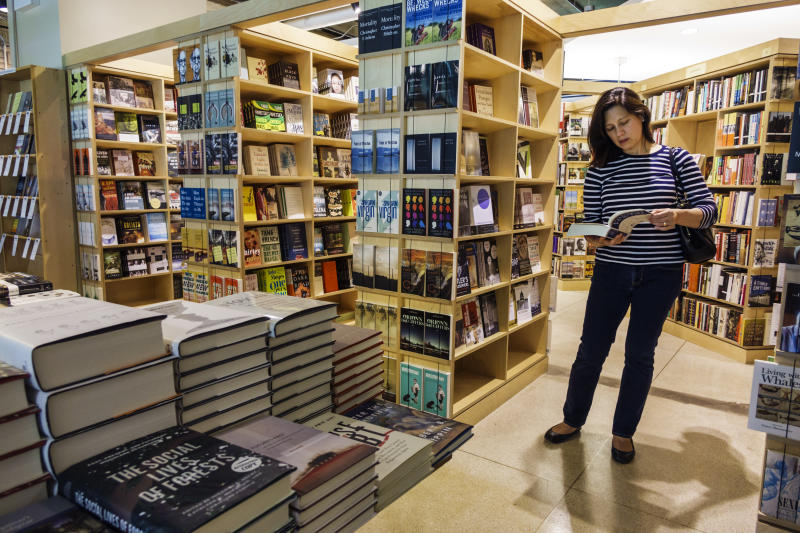 A woman looking at a textbook in the Seminary Co-op Bookstores at University of Chicago. (Photo by: Jeffrey Greenberg/Universal Images Group via Getty Images)