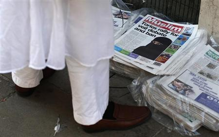 A man looks at newspapers outside the Brick Lane Jamme Masjid before Friday prayers in east London