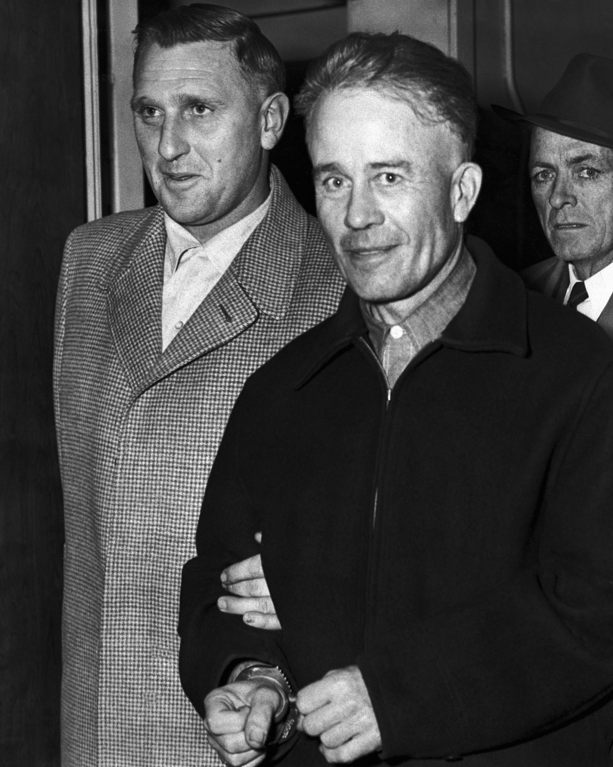 Serial killer Ed Gein is escorted from the Wisconsin State Crime Laboratory to the county jail after confessing to two murders.