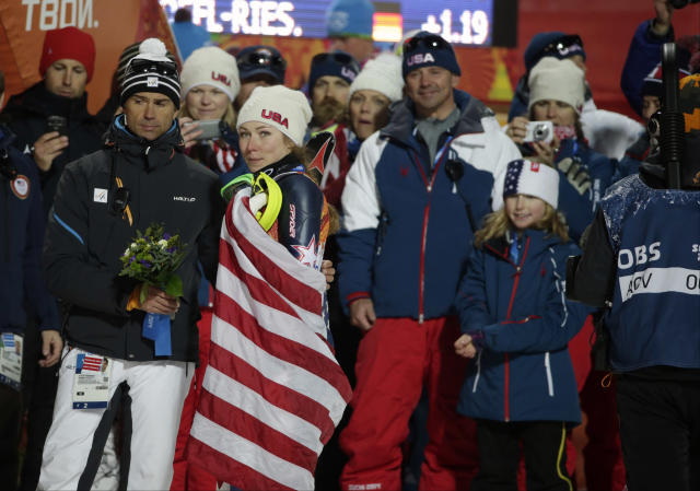 Women's slalom gold medal winner United States' Mikaela Shiffrin is draped in the American flag after a flower ceremony at the Sochi 2014 Winter Olympics, Friday, Feb. 21, 2014, in Krasnaya Polyana, Russia. (AP Photo/Gero Breloer)