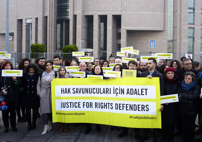 Turkish and international human rights activists face the media before the trial of the Amnesty International's former Turkey chairman and 10 other activists, in Istanbul, Wednesday, Feb. 19. 2020. A court in Istanbul will hand down verdicts for defendants in the closely-watched trial on charges of belonging to or aiding terror groups. The case against activists heightened concerns about Turkey's treatment of human rights defenders. (AP Photo)