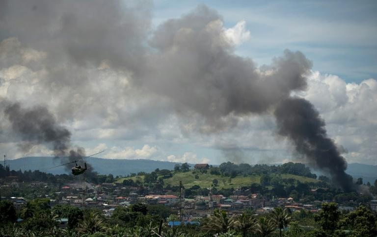 A helicopter flies through smoke billowing from houses after the Philippine air force bombed Islamist militant positions in Marawi