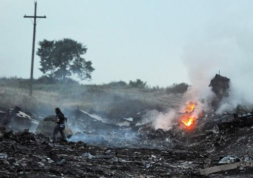 <p>People stand amongst the wreckage of the Malaysia Airlines plane after it crashed near the town of Shaktarsk, in rebel-held east Ukraine on July 17, 2014</p>