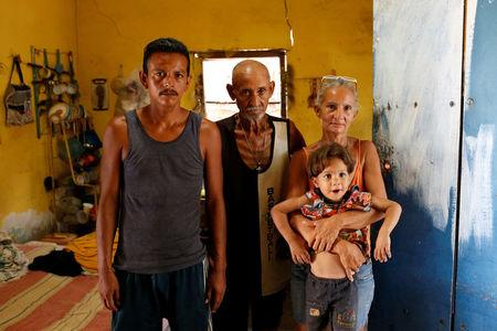 Zulay Pulgar (R), 43, holds her son Emmanuel, 4, next to her husband Maikel Cuauro (L), 30, and her father Juan Pulgar, 73, while they pose for a portrait in their house in Punto Fijo, Venezuela November 17, 2016. Picture taken November 17, 2016. REUTERS/Carlos Garcia Rawlins