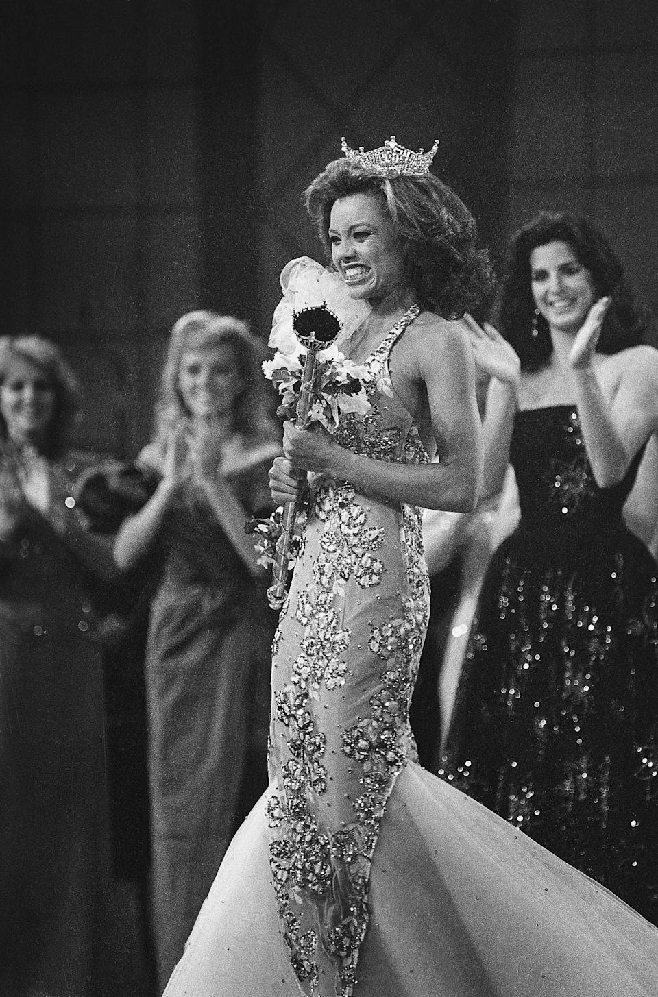 Crowned the new Miss America 1984, Miss New York, Vanessa L. Williams beams as she is applauded by runners-up Miss Virginia, Lisa Aliff (left), and Miss Ohio, Pamela Rigas (right). Williams is the first black woman to have won the crown in the pageant's 63-year history.