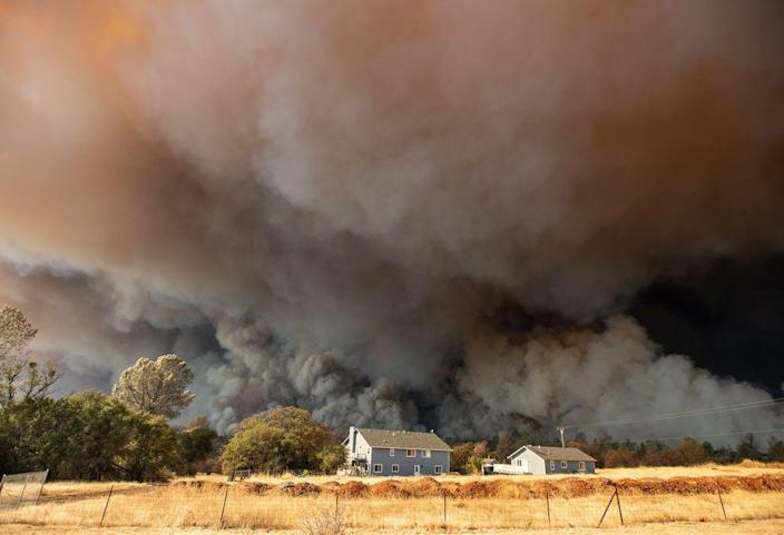 A home is overshadowed by towering smoke plumes as the Camp fire races through town in Paradise, Calif. on Nov. 8.