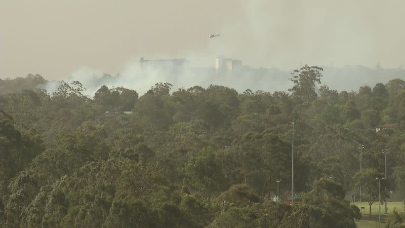 A helicopter flies over a bushfires in South Turramurra