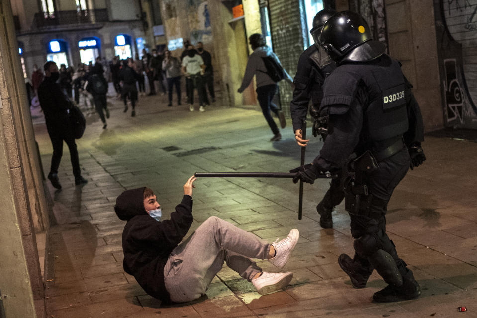 Police clash with protesters in downtown Barcelona, Spain, Friday, Oct. 30, 2020. Clashes have erupted in a central Barcelona square between anti-riot police and hundreds who had gathered to protest the mandatory closure of bars, restaurants and other businesses in the latest effort to rein in on coronavirus outbreaks. (AP Photo/Emilio Morenatti)