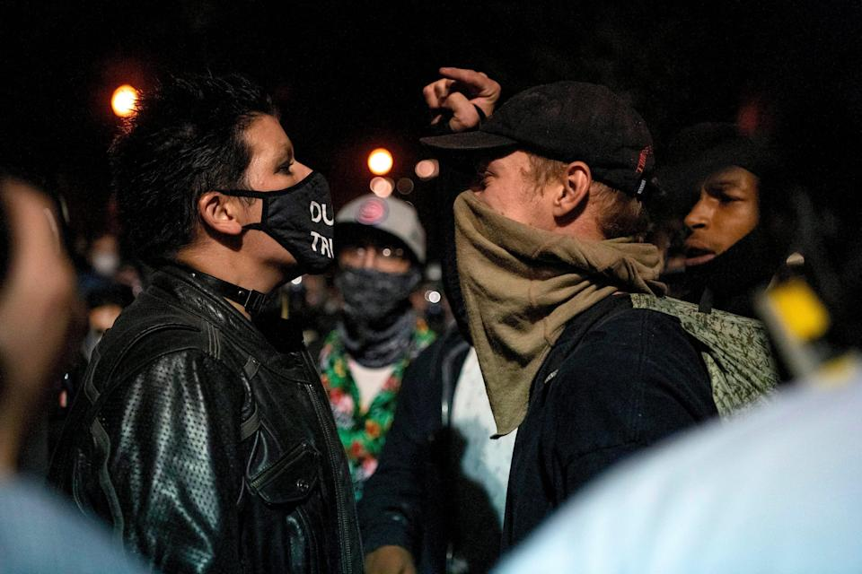 Demonstrators confront one another after one group put out a fire during a night of protest on July 31, 2020 in Portland, Oregon.