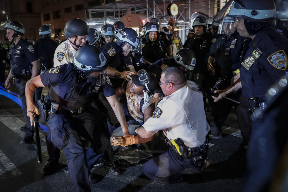 FILE — In this June 4, 2020 file photo, a protester is arrested on New York's Fifth Avenue by NYPD officers during a march, following the death of George Floyd. The New York Police Department was caught off guard by the size and scope of the spring protests sparked by the police killing of George Floyd in Minneapolis and resorted to disorder control tactics that stoked tensions and stifled free speech rights, the city's inspector general said in a report released Friday, Dec. 18, 2020. (AP Photo/John Minchillo, File)