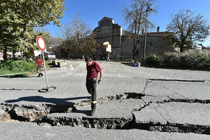 A fireman looks at cracks in the road outside Norcia, central Italy after a 6.6 magnitude earthquake struck on October 30, 2016 (AFP Photo/Alberto Pizzoli)