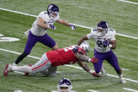 Northwestern running back Cam Porter (20) runs with the ball as Ohio State defensive tackle Haskell Garrett defends and teammate John Raine (0) watches during the first half of the Big Ten championship NCAA college football game, Saturday, Dec. 19, 2020, in Indianapolis. (AP Photo/Darron Cummings)