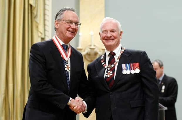 Retired Supreme Court of Canada justice Ian Binnie (L) shakes hands with Governor General David Johnston after being awarded the rank of Companion in the Order of Canada at Rideau Hall in Ottawa on November 23, 2012.