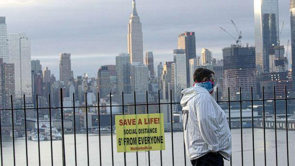 PHOTO: A man wears a face mask as he walks with the Manhattan skyline behind him, April 6, 2020, as seen from Weehawken, New Jersey. (Kena Betancur/Getty Images)