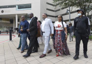 Attorney Ben Crump, second from left, walks with Ron Lacks, left, Alfred Lacks Carter, third from left, both grandsons of Henrietta Lacks, and other descendants of Lacks, whose cells have been used in medical research without her permission, outside the federal courthouse in Baltimore, Monday, Oct. 4, 2021. They announced during a news conference that Lacks' estate is filing a lawsuit against Thermo Fisher Scientific for using Lacks' cells, known as HeLa cells. (AP Photo/Steve Ruark)