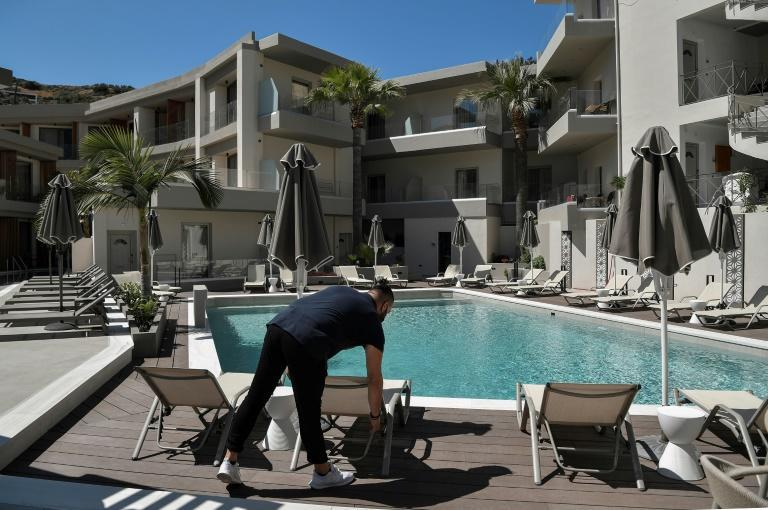 Hotel owner Kostantinos Kouratoras, adjusting a sunbed at his hotel in the fishing village of Bali. says 'a difficult but eventually positive season lies ahead'