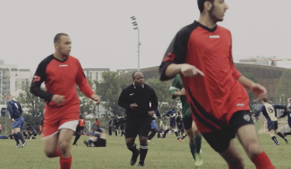 This grab taken from video taken on Aug. 23, 2015, shows Jermaine Wright, centre, a NHS pharmacist and a referee of the Hackney Marshes grassroots football league overseeing a match. Wright, affectionately known as Mr. Hackney Marshes, served as both an on-field referee and a behind-the-scenes catalyst in the Hackney & Leyton Sunday Football League — as vice chairman, schedule secretary, results secretary, press officer, and head official before he died on April 27, 2020 from COVID-19. (Thomas Wootton via AP)