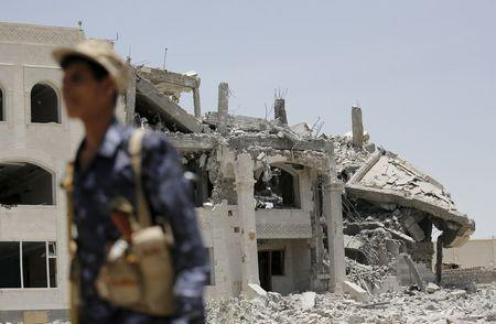 A Houthi militant walks at the yard of residence of the military commander of the Houthi militant group, Abdullah Yahya al Hakim, after it was hit by an airstrike, in Sanaa April 28, 2015. REUTERS/Khaled Abdullah