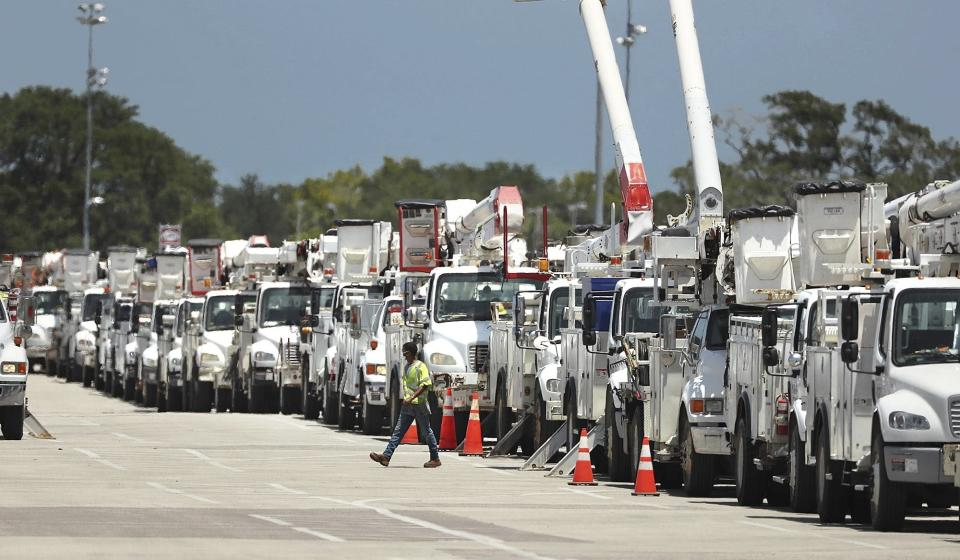 Dozens of utility trucks are lined up to be processed by Florida Power & Light at Daytona International Speedway on Saturday, Aug. 1, 2020. Thousands of electric lineman crews and other employees were processed at the site to be sent to staging centers in preparation for Hurricane Isaias. Isaias snapped trees and knocked out power as it blew through the Bahamas on Saturday and weakened to a tropical storm as it churned toward the Florida coast, where it still threatened to complicate efforts to contain the coronavirus in a hot spot. (Stephen M. Dowell/Orlando Sentinel via AP)