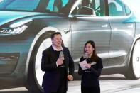 Tesla Inc's Elon Musk and Grace Tao attend a delivery ceremony for the EV maker's China-made Model 3 cars in Shanghai