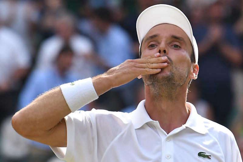Spain's Roberto Bautista Agut celebrates after beating Argentina's Guido Pella during their men's singles quarter-final match on day nine of the 2019 Wimbledon Championships at The All England Lawn Tennis Club in Wimbledon southwest London