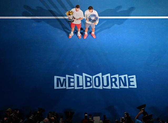 2014 Australian Open tennis tournament winner Stanislas Wawrinka (top L) poses with the trophy next to the runner-up Rafael Nadal, in Melbourne, on January 26, 2014 (AFP Photo/William West)