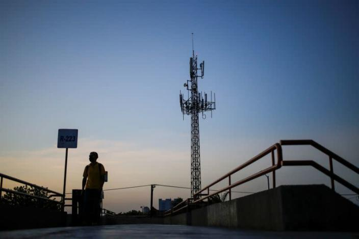 A man walks by near a cellular tower in the municipality of Guadalupe