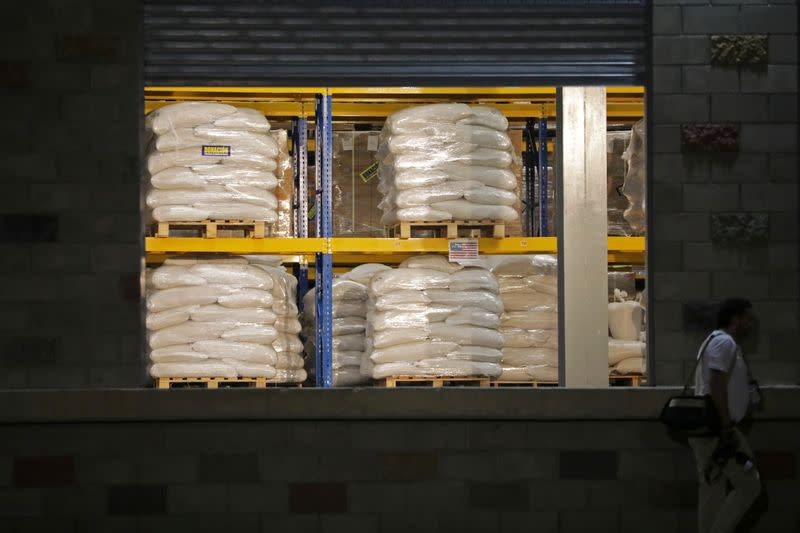 FILE PHOTO: A man walks past aid at a warehouse where international humanitarian aid for Venezuela is being stored, during a visit by U.S. Secretary of State Mike Pompeo and Colombia's President Ivan Duque, in Cucuta