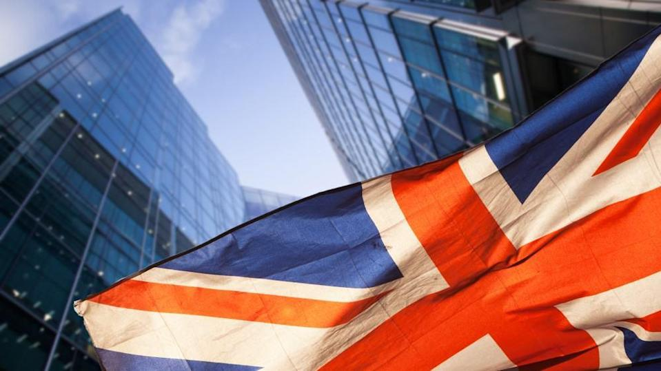 The UK national flag in front of Canary Wharf skyscrapers where professionals trade shares for a living.