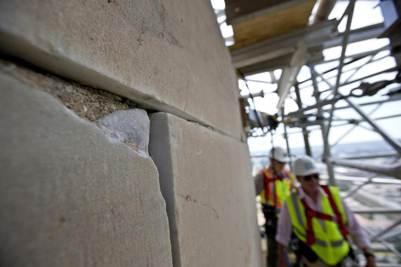 FILE – In this June 2, 2013, file photo earthquake damage, a missing corner of a stone, is seen on the Washington Monument at the 491-foot level of the scaffolding encompassing it in Washington. While the Monument's earthquake damage is being repaired over the next year, 488 lamps will restore the tower's glow each night on the National Mall starting Monday, July 8, 2013. (AP Photo/Alex Brandon, File)