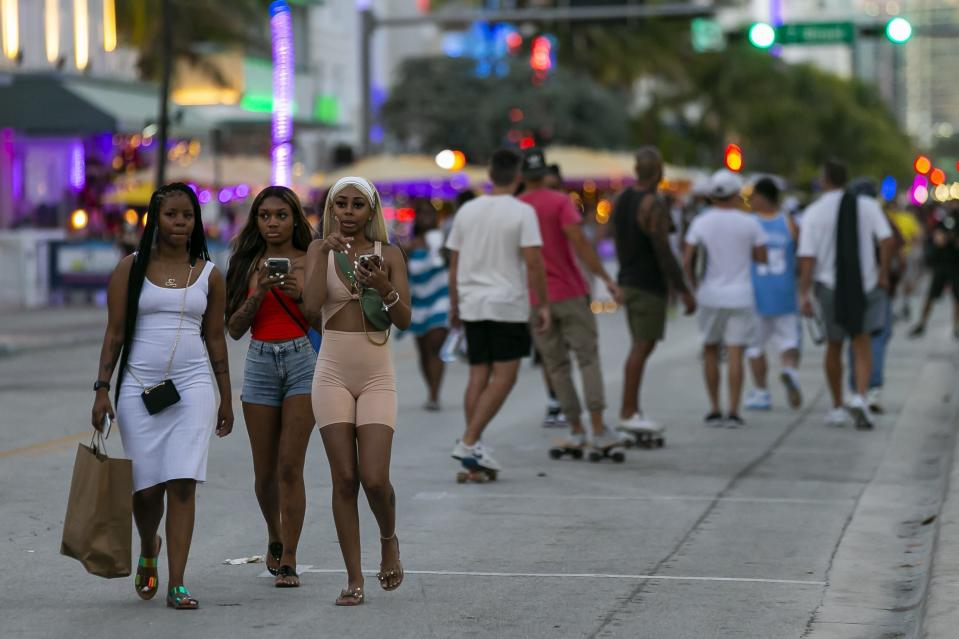 Tourists make their way down Ocean Drive during Spring Break in Miami Beach, Fla., Monday, March 22, 2021. A party-ending curfew is in effect in Miami Beach, imposed after fights, gunfire, property destruction and dangerous stampedes broke out among huge crowds of people. The curfew could extend through the end of spring break.(Matias J. Ocner/Miami Herald via AP)
