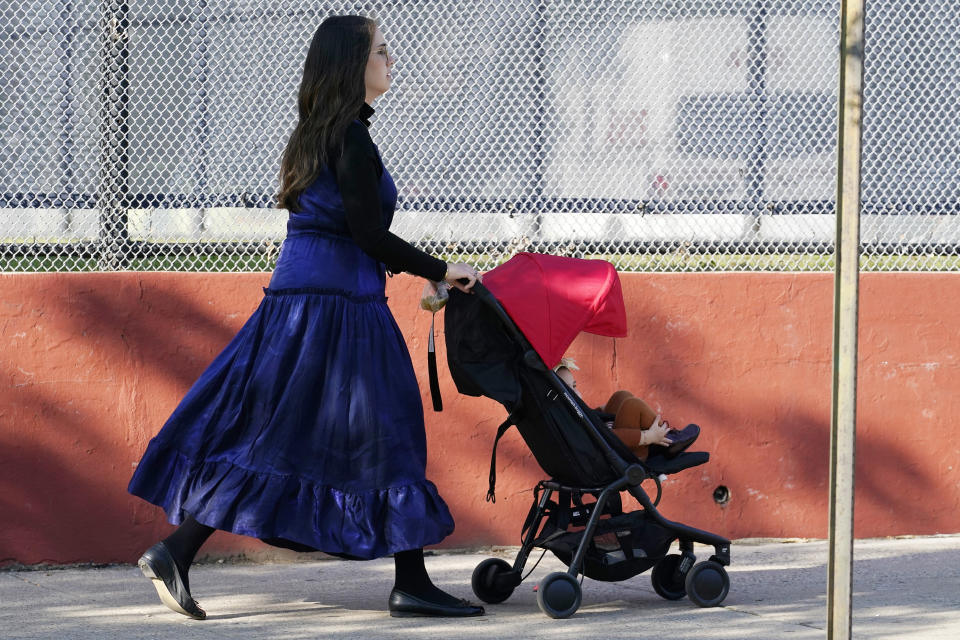 A woman walks with a child, Sunday, Oct. 4, 2020, through the Borough Park neighborhood of New York, one of nine zip codes to have recently seen a rise in cases of coronavirus. New York City's mayor said Sunday that he has asked the state for permission to close schools and reinstate restrictions on nonessential businesses in several neighborhoods because of a resurgence of the coronavirus. (AP Photo/Kathy Willens)