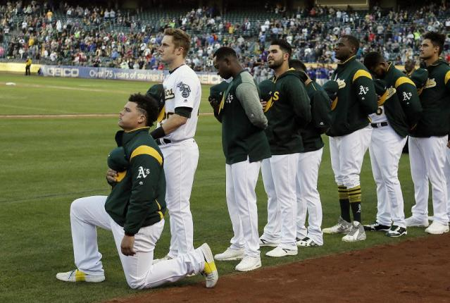 Oakland Athletics catcher Bruce Maxwell kneels during the National Anthem before the start of a baseball game against the Texas Rangers Saturday, Sept. 23, 2017, in Oakland, Calif. (AP Photo/Eric Risberg)