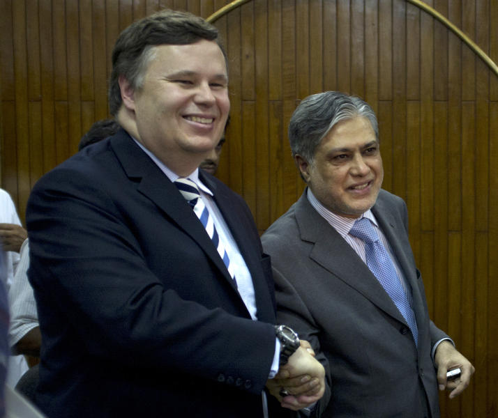 Pakistani Finance Minister Muhammad Ishaq Dar, right, shakes hands with IMF mission chief Jeffrey Franks after a joint news conference in Islamabad, Pakistan on Thursday, July 4, 2013. Pakistan and the International Monetary Fund have reached an initial agreement on a bailout of at least $5.3 billion to stave off an economic crisis as the country's foreign reserves dip perilously low, officials said Thursday. (AP Photo/B.K. Bangash)