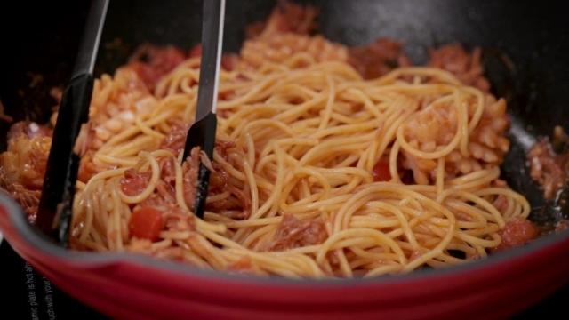 Stir frying spaghetti in a pan with tongs
