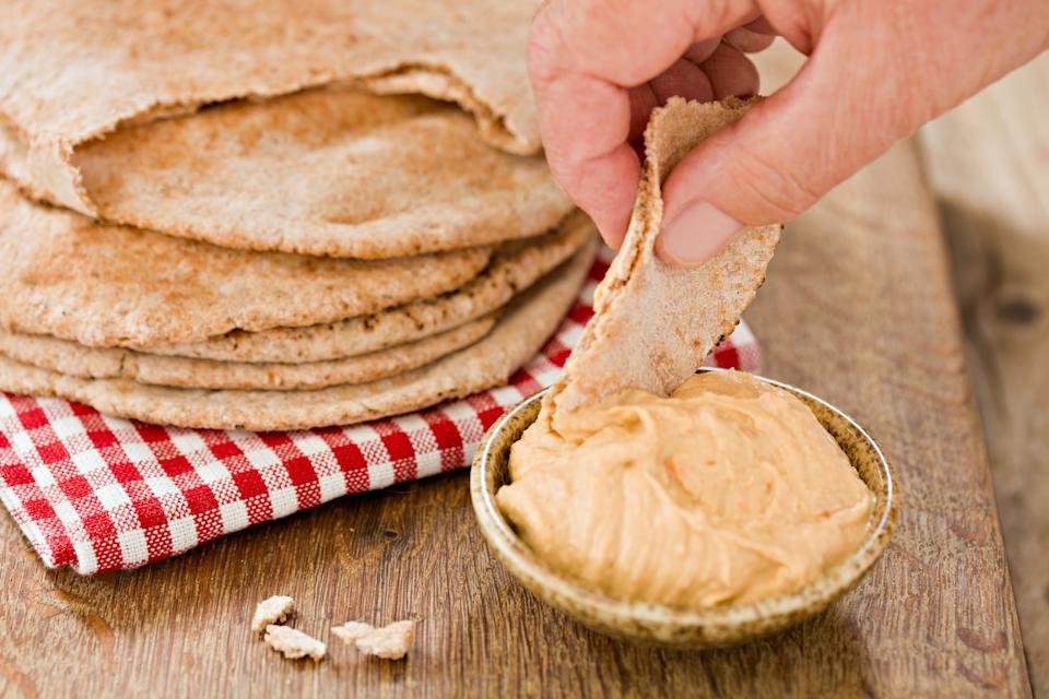 A close up shot of a hand dipping a piece of pitta brad into some hummus. Shot against a wooden background.