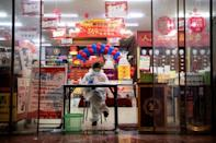 A vendor wears protective gear in Yueyang, Hunan province, China, where massive quarantine efforts have paid off