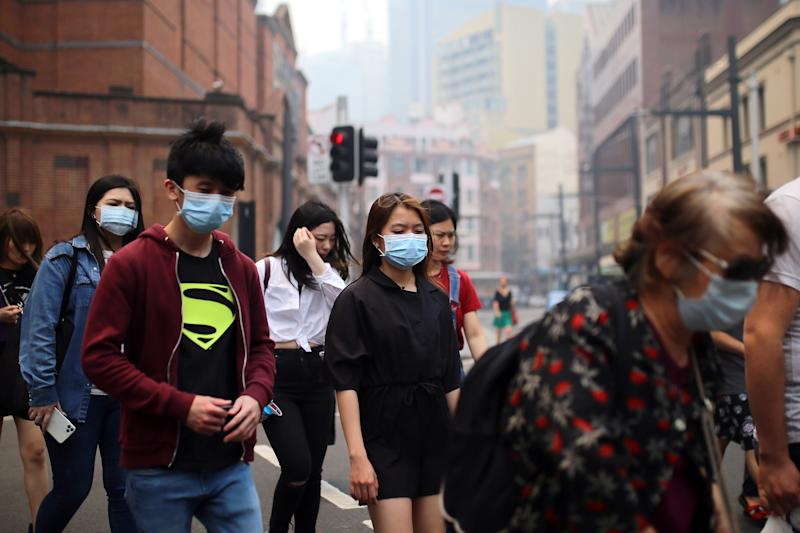 Pedestrians are seen wearing masks as smoke haze from bushfires in New South Wales blankets the CBD in Sydney, Tuesday, December 10, 2019. Source: AAP