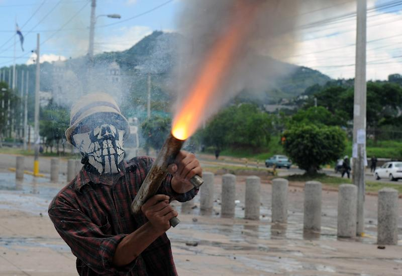 A student from the National Autonomous University of Honduras (UNAH) fires a homemade gun during clashes with the police in Tegucigalpa on November 4, 2015 (AFP Photo/Orlando Sierra)