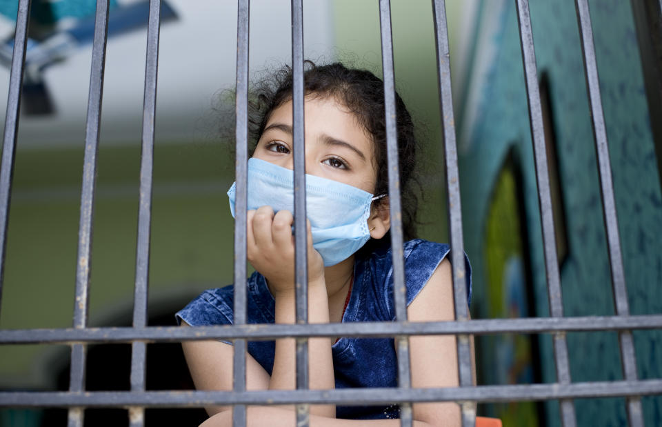 Little girl wearing a face mask and peeking out from window