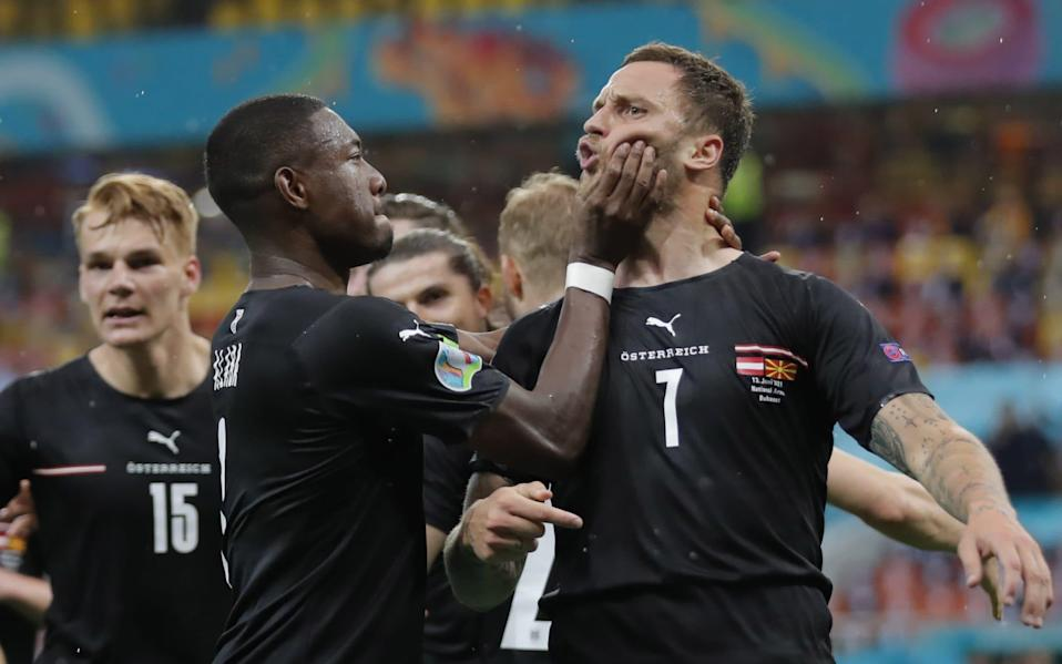 Marko Arnautovic (right) is restrained by Austria teammate David Alaba after scoring against North Macedonia - SHUTTERSTOCK