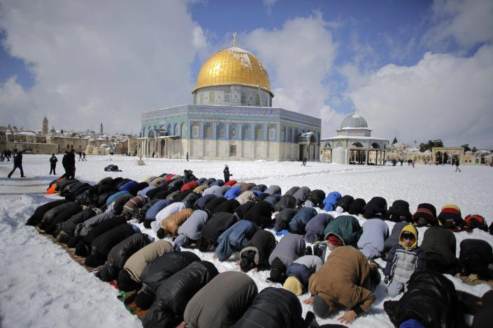 Palestinian men pray in front of the snow-covered Dome of the Rock on the compound known to Muslims as Noble Sanctuary and to Jews as Temple Mount, in Jerusalem's Old City February 20, 2015. Snow fell early Friday morning in parts of Israel, including Jerusalem, and various towns and cities in the north and south of the country, causing school closures in areas affected by the weather. (REUTERS/Ammar Awad)