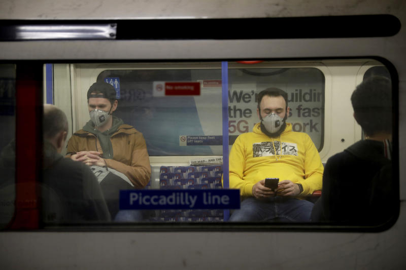 Men wearing face masks travel on a Piccadilly Line underground train in London, Friday, March 20, 2020. For most people, the new coronavirus causes only mild or moderate symptoms, such as fever and cough. For some, especially older adults and people with existing health problems, it can cause more severe illness, including pneumonia. (AP Photo/Matt Dunham)
