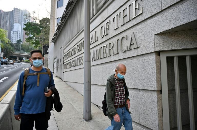 People walk past the US consulate building in Hong Kong following its temporary closure