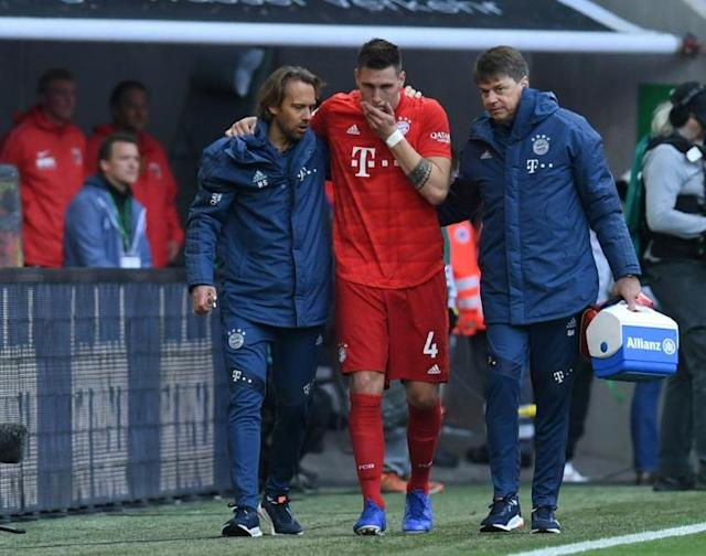 Niklas Suele was helped off after injuring his knee as Bayern drew at Augsburg (AFP Photo/Christof STACHE)